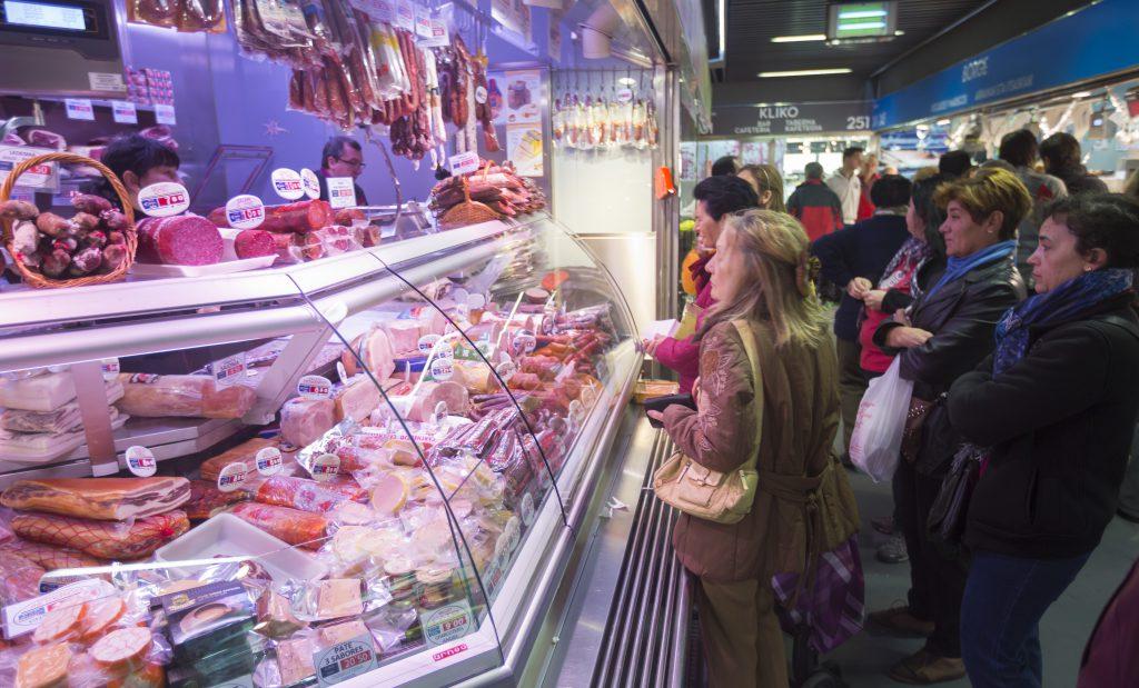 Puesto de carnicería del Mercado de la Ribera con gente comprando